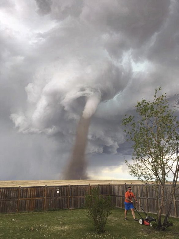 Photo credit: Theunis Wessels mows his lawn in Three Hills in Alberta, Canada, on June 2 as a tornado swirls in the background. CECILIA WESSELS/CANADIAN PRESS/AP